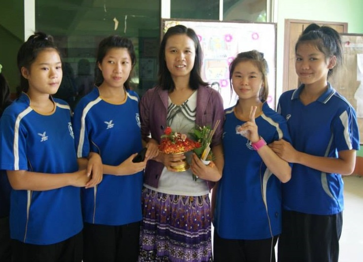 Grade 5 girls pose with HDS head teacher P'Oi